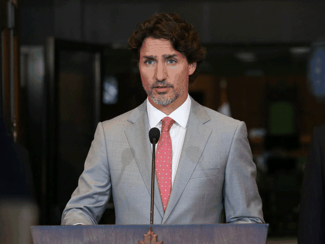 Prime Minister Justin Trudeau in a tan suit speaking to reporters